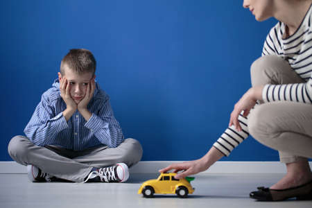 Foto de Kid is looking on yellow toy car while sitting with crossed legs on white floor - Imagen libre de derechos