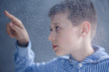 Foto de Autistic child in blue shirt is looking on drops of water on window in home - Imagen libre de derechos
