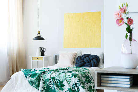 Photo pour Guest bedroom with green tropical bedding and yellow artwork - image libre de droit