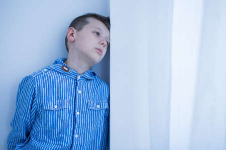 Foto de Worried boy rests his head on white wall and spends afternoon alone at home - Imagen libre de derechos