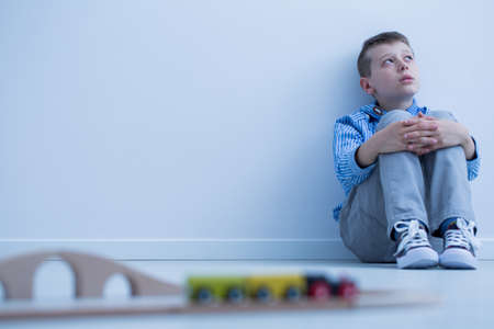 Foto de Boy in blue shirt sitting on floor and starring at wall, doesn't want to play with electric train - Imagen libre de derechos