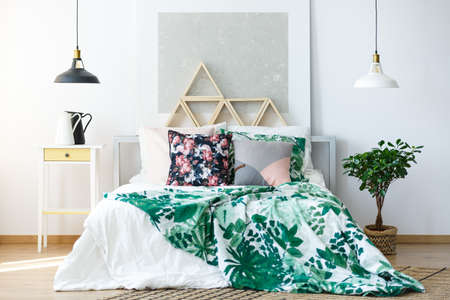 Foto de Natural colored bedroom with delicate furniture and botanical prints - Imagen libre de derechos