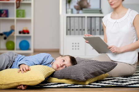 Foto de Boy is lying on brown and yellow pillows in classroom during meeting with psychologist - Imagen libre de derechos