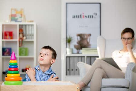 Foto de Pedagogue sits on grey armchair and observes boy sick of Haller's syndrome. Autistic child therapy concept - Imagen libre de derechos