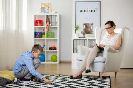Foto de Child sits on black and white carpet while psychotherapist is observing him. Autistic child therapy concept - Imagen libre de derechos