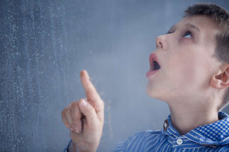Foto de Boy in blue shirt with asperger's syndrome stands by window and watches rain drops - Imagen libre de derechos