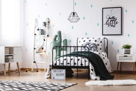 Foto de Toy in shape of cactus next to bed with black blanket and grey braided pillow in kids room with painting - Imagen libre de derechos