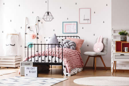 Photo pour Colorful pillows on knit pink blanket on bed in cute kids bedroom with posters on wall - image libre de droit