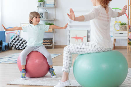 Photo pour Physiotherapist and young boy doing stretching exercise on colorful balls in bright room - image libre de droit