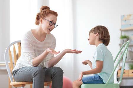 Foto de Smiling psychotherapist talking with autistic boy sitting on mint chair during psychotherapy - Imagen libre de derechos