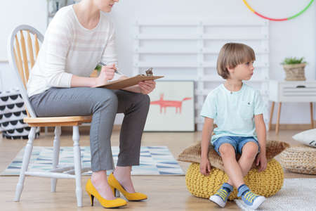 Foto de Misbehaving boy sitting on a yellow pouf during meeting with counselor in colorful classroom - Imagen libre de derechos