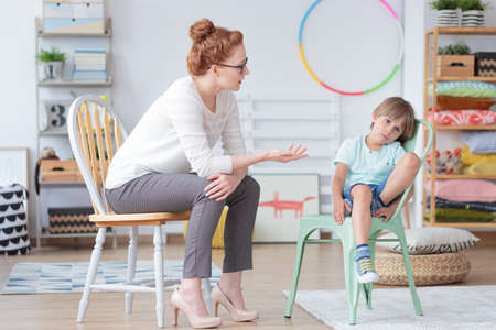 Foto de Red haired counselor talking with worried boy sitting on mint chair in colorful room with toys - Imagen libre de derechos