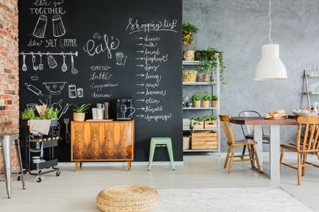 Photo pour Dining room with chalkboard wall, wooden chest and kitchen cart - image libre de droit