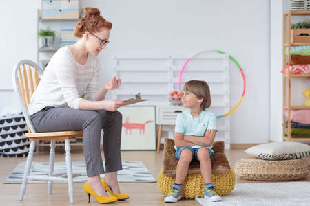Photo pour Young boy sitting on a yellow pouf with crossed arms listening to his psychotherapist during session - image libre de droit