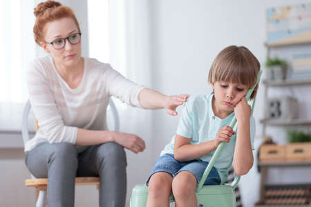 Foto de Sad autistic boy sitting on a mint chair during session with red haired psychotherapist - Imagen libre de derechos