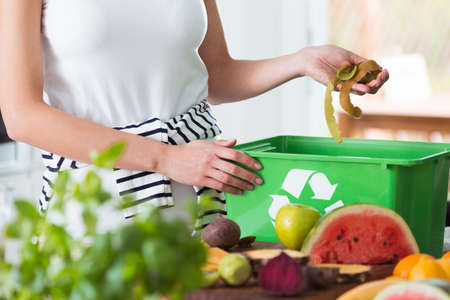 Photo pour Woman recycling organic kitchen waste by composting in green container during preparation of meal - image libre de droit