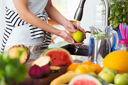 Photo pour Healthy woman washing an apple above kitchen sink while preparing fresh breakfast with fruit - image libre de droit