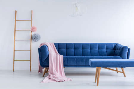 Foto de Colorful pompoms on ladder next to navy blue sofa with pink blanket in living room with stool - Imagen libre de derechos