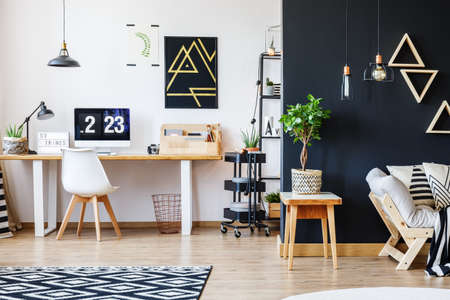 Photo for Nordic natural interior in stylish open studio for a freelancer with sofa, black wall and office space with desk and black accent - Royalty Free Image