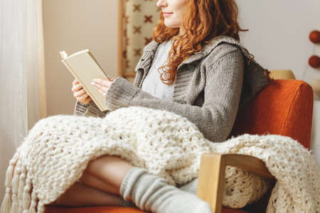 Photo for Happy young woman reading a book in a chair - Royalty Free Image