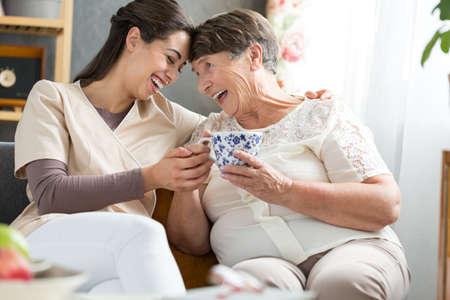Foto de Two women laughing together at a funny joke during afternoon tea break in retirement home - Imagen libre de derechos