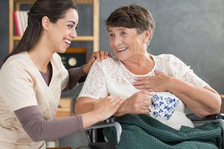 Foto de Retired woman in wheelchair talking to happy nurse and drinking tea from a white mug with floral pattern - Imagen libre de derechos