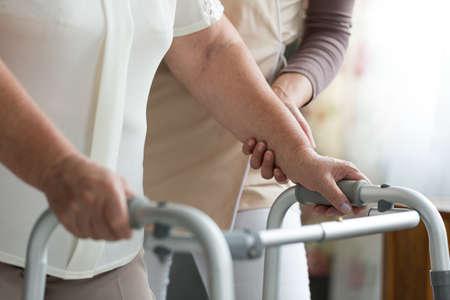 Foto de Elder woman trying to walk using a walker during physiotherapy with support of a nurse - Imagen libre de derechos