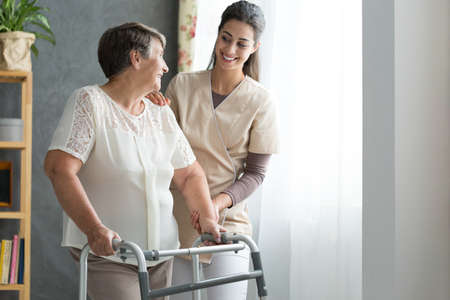 Photo for Smiling nurse helping senior lady to walk around the nursing home - Royalty Free Image