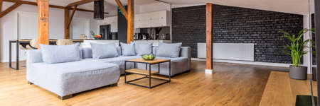 Photo pour Modern loft open space apartment with wooden beams and floor, simple modern furniture, gray sofa, coffee table, brick wall, view from the living room - image libre de droit