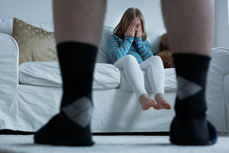 Foto de Scared oppressed girl hiding from her father, pathological family concept - Imagen libre de derechos