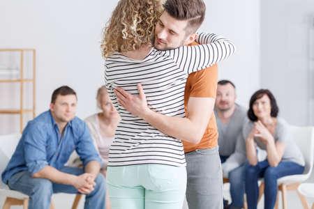 Foto de Young caucasian couple hugging during group marital therapy - Imagen libre de derechos
