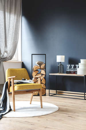 Photo pour Wooden yellow armchair with blanket standing on white rug in stylish living room with wood logs, black wall and gray curtains - image libre de droit