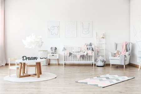 Foto de Pink blanket on grey armchair in pastel kid's room with small table and plush toy on white cabinet - Imagen libre de derechos
