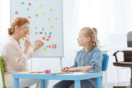 Foto de Speech therapist practicing correct mouth position with girl while sitting at blue table during speech therapy - Imagen libre de derechos