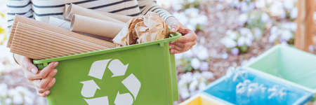 Foto de Eco-friendly person taking care of ecosystem by sorting paper to green container. Recycling concept - Imagen libre de derechos