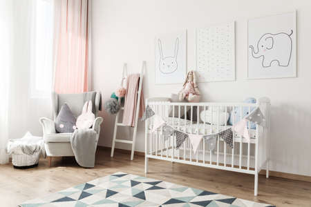 Photo pour White baby's bed with banner and pillows against white wall with pictures in room with ladder and grey armchair - image libre de droit