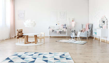 Photo pour Designer white lamp above small table with plush bear on chair in baby's room with rocking horse - image libre de droit