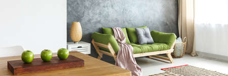 Photo for Pink blanket and grey pillow on green sofa against concrete wall in natural living room with lamp on shelf - Royalty Free Image