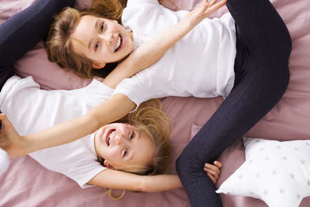Photo for Happy, little siblings playing together in bed - Royalty Free Image