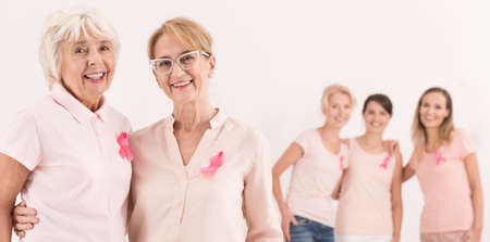 Photo pour Three young women stand behind two happy and confident elderly. Breast cancer concept - image libre de droit