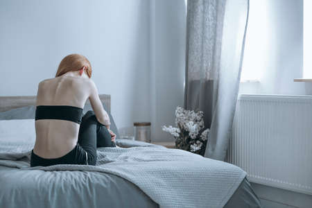 Foto de Overly thin girl despairing over her large weight loss while sitting on a bed with her spine sticking out of her neck - Imagen libre de derechos