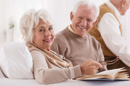 Photo for Happy elder is looking at wife which is reading book in bright room - Royalty Free Image