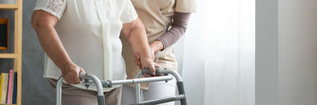 Foto de Professional assistant supporting elderly woman in white shirt using walker in living room - Imagen libre de derechos