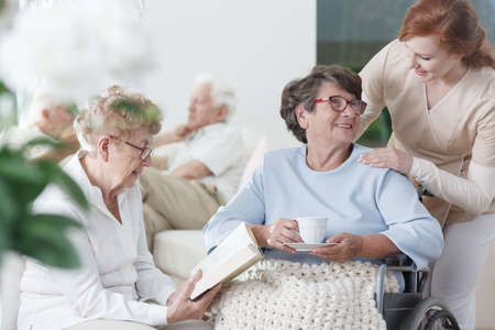 Foto de Two elder ladies in glasses spending time together in common room of nursing home - Imagen libre de derechos