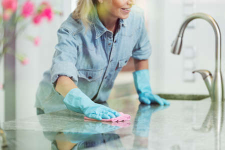 Photo for Pedantic woman wiping down kitchen countertop with pink cloth, wearing blue jean shirt and rubber gloves for household cleaning - Royalty Free Image