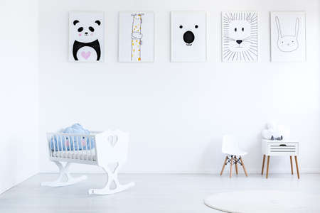 Foto de Blue pillow in white cradle in simple baby's bedroom with small chair and cabinet against wall with animal posters gallery - Imagen libre de derechos