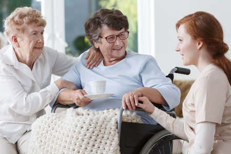 Foto de Caucasian nurse in uniform talking to her patient in wheelchair and her visiting sister - Imagen libre de derechos