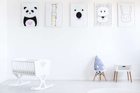 Foto de White cradle in baby's bedroom with blue pillow on small chair next to cabinet against wall with animal posters gallery - Imagen libre de derechos