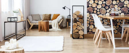 Photo for Warm multifunctional room with sofa and dining table against wall with log wallpaper - Royalty Free Image