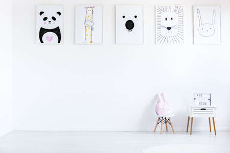 Foto de Pastel pillow on small chair next to cabinet against wall with autistic kid drawings in white room, copy space concept - Imagen libre de derechos